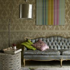 so chic, love the couch, the chair rail and the wallpaper, especially mixed with the modern lamp, painting and footstool.