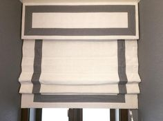 Custom cornice and Roman shade by August Taylor Design with trim by Samuel and Sons.