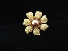 Adorable flower ring with gold and brown rhinestones and a brown colored pearl in the center.  It's a size 8 but can be adjusted to be bigger