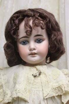This is one of the prettiest dolls Armand Marsielle manufactured. Her head has no cracks or chips and is marked 1894 DEP AM. Her blue paperweight eyes are beautiful. She has heavy stacked brows, painted upper and lower lashes, open mouth with 4 teeth. She has her original antique mohair wig. Her composition body has the original finish with some touch up at the shoulders (see pictures). She is dressed in a silk dress with lots of lace, flower and antique broach. Comes with pantaloons, shoes…