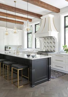 Well design white and black kitchen features three Nuevo Chi Counter Stools placed at a black center island topped with a calcutta quartz countertop finished with a farmhouse sink paired with a polished brass deck mount faucet.