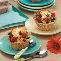 """Tricky Taco Cups Recipe-Fools of all ages will fall in love with these sensationally sneaky sweets that look like taco salads. Crunchy waffle bowls are filled with chocolate ice cream, then topped with tinted coconut """"lettuce"""" and """"cheese"""", maraschino cherry """"tomatoes"""" and black licorice """"olives""""."""