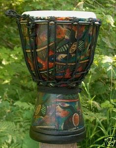 """Tribal Motif Sarong Design Djembe Drum- 11""""-12"""" Tall x 7""""-8"""" Head by Mother Rhythm Drums. $35.00. Tribal Motif Sarong design djembe drum. Sarong material is laminated to the surface of the wooden drum shell giving it a durable and water-resistant attractive appearance. Made of one-piece mahogany and goat skin, and typically measures anywhere between 11-12 inches tall, with overall diameters of 7-8 inches, and playing surface diameters of 6-7 inches. Roped tight with 4..."""