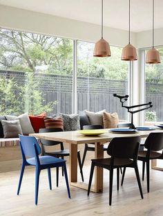 rechteckiger Esstisch, bunte Stühle und Sitzbank am Fenster