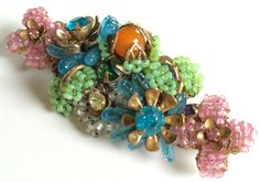 Here is an absolutely exquisite vintage brooch pin by designer Miriam Haskell. It is crafted in a most decadent and intricate floral pattern  $750