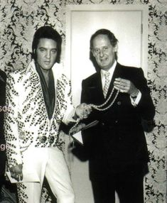 Elvis in his hotel suite in Las Vegas on September 1, 1973 being presented a long torsaded gold chain by Henry Levin of the Hilton. The chain was then used on stage by Elvis for all his shows until the end of the engagement. Also pictured with Elvis is his father Vernon and George Parkhill of RCA Records
