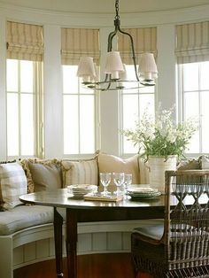 An oval table is ideal in this country breakfast nook with the half moon shaped banquet.