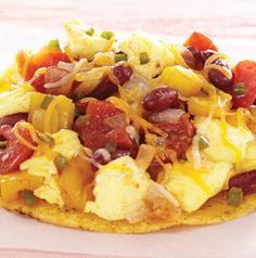 Need a hearty filling breakfast idea? Huevos Rancheros fits the bill! Tostada shells are topped with scrambled eggs and a spicy tomato and bean mixture. Of course, you've got to sprinkle it with cheese!