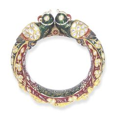 AN INDIAN ENAMEL AND DIAMOND KADA BANGLE   Designed as two opposing green enamel birds, with table-cut diamond wings and eyes, the blue, green and red enamel tails decorated with table-cut diamond foliate clusters, forming the hinged hoop, to the polychrome enamel inner border of foliate design, 2 3/8 ins. diameter