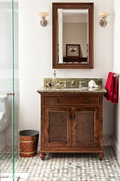 """This Ensuite designed for a teenage boy is masculine but not boring - inspired by the British Raj, this ensuite has a """"clubby"""" feel to it. The key elements are the patterned green, custom floor tiles and coordinating marble top, the textured cane vanity, the Waterworks AstoriaFaucet and another one of my signatures - a pair of vintage sconces. The result: abathroom that has no age limits! Designed by Casey Design."""