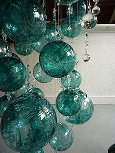 "Hang turquoise and sea foam green glass ball ornaments of multiple sizes for a  ""wow"" decor idea for above the reception area or dance floor"