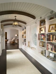 This is a hallway, believe it or not. Beadboard ceiling, dark painted curved beams to match, built in bookcases, round window, dark floor, cool light. Ok, I'm there.