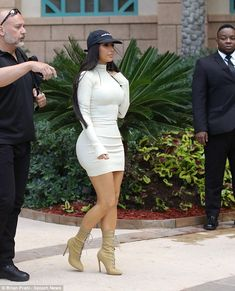 Looking bootyful! Kim Kardashian shows off her shapely rear in a form fitting white dress as she heads out in Dubai on Saturday