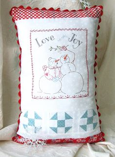 """Pucker up under the mistletoe with our sweet Snowman couple! This 13 1/2"""" x 20"""" pillow links simple piecing with the perfect stitchery for a beginning stitching class. Nine stitches and a little bit of beading make this a fun project for everybody!"""