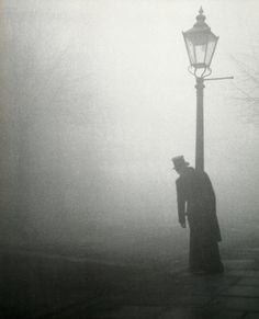 Man in the mist leans against a lamppost