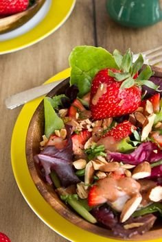Spring salad with strawberry lemon basil dressing and almonds, coconut, and fresh basil
