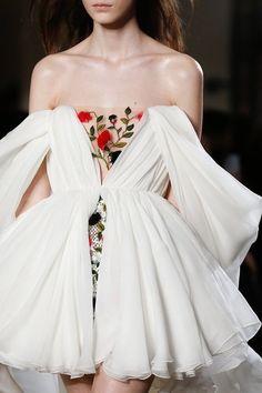 Floral sheer panel on white off-the-shoulder dress.