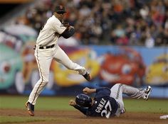 San Francisco Giants second baseman Joaquin Arias, left, jumps over Milwaukee Brewers' Carlos Gomez to complete a double play in the second inning of a baseball game on Wednesday, Aug. 7, 2013, in San Francisco. Brewers' Khris Davis was out at first base. (AP Photo/Ben Margot)