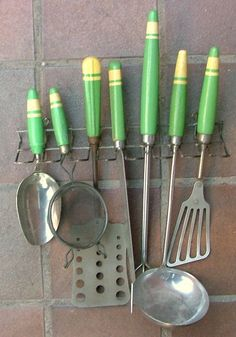 This was advertised on eBay as 'Home Front 1940s Kitchen Skyline utensil set sold in Britain'.  However, this was a popular color combination and banded design in the U. S. during the 1930s.  A prolific USA manufacturer was the A & J Company which always stamped their logo on the metal part of the utensils.