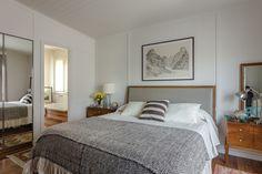 Impronta de los ´50  En el dormitorio principal, cama con respaldo tapizado en cuero y mesas de luz de raíz de laurel