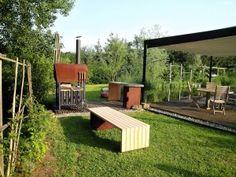 Gartengestaltung aus Cortenstahl mit Lärche. Bank, Anrichte und Holzbackofen.