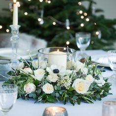 Nordic Table Wreath from our Christmas 2016 collection.  This Winter White Christmas table arrangement creates the perfect table centre piece.  It has Cream Piaget, Vitality & White O'hara roses.  Here we've styled this Christmas table wreath with a crisp white tablecloth, crystal glass and silver accessories.