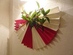 こちらは扇子風のお正月飾り! 材料はほとんど100円均一でそろうものばかり。  (1)白と赤の画用紙を張り合わせて、扇子のように折る  (2)金色の水引きで縛り、水引きの鶴を飾る (どちらも100円均一などで売っています!)  (3)千両をあしらう