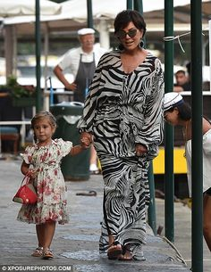 Doting grandma: Kris wore a stylish zebra-print maxi dress as they strolled…