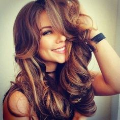 Great looking full bouncy curls with blonde highlights in her brunette hair.