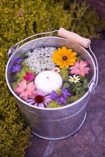 bucket filled with flowers and floating candle - great decor for outdoor party, especially if I can find a citronella one