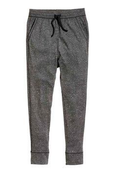 Calças de treino: Calças de treino com elástico e cordão de ajuste na cintura e pernas estreitas. Têm bolsos laterais, um bolso atrás, gancho baixo e barra em malha canelada no remate das pernas.