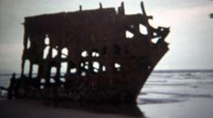 1971: Rusty broken old shipwreck beached on sandy ocean shore. http://www.pond5.com/stock-footage/59871236?ref=StockFilm keywords:1971, Rusty, broken, old, shipwreck, beached, sandy, ocean, shore, 1970s, 8mm, film, home movie, vintage, retro, rare, unique, archival, Americana, documentary, editorial, history, classic, Wreckage, rusted, washed up, ashore, wreck, sunk, water, damage, beach, sea, warship, skeleton, sailing, boat, eroded