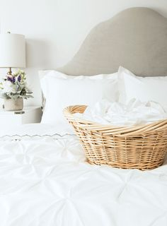 White bedding, wicker laundry basket, and white sidetable with lamp