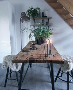 Gorgeous rustic Scandinavian kitchen table. The potted plant and candles add the perfect touch of simple, country calm.