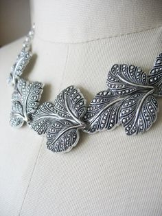 A gorgeous example of vintage Eloxal aluminum jewelry. This piece features large faux marcasite leaves in a draping choker style necklace. Tons of