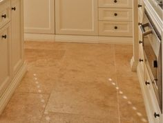 Cream cabs with existing travertine flooring...need to add more decorative trim at the bottom of my cabs