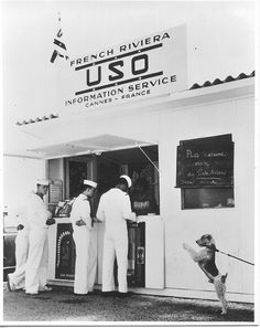 Sailors standing outside the French Riviera USO information services center. Cannes, France in 1940. Cute pup.