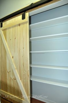 Barn door on track with rolling hardware. Go to Tractor Supply Co. for less expensive hardware.
