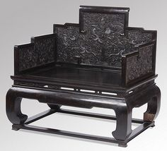 Carved zitan throne armchair with stepped back and arms embellished with dragons, waves and rockwork, the back with a central facing dragon surrounding a flaming pearl over a seat raised on elephant legs, China 18th Cent.