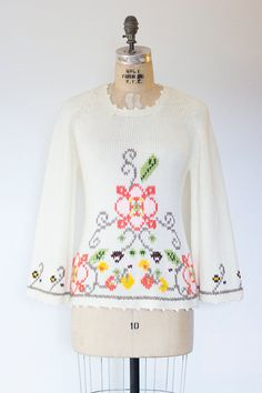 Vintage 1970s cream acrylic sweater with floral cross-stitch looking pattern, wide bell sleeves and a scoop neck. Cute fitted shape and super soft!  ✂