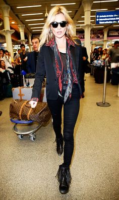Kate Moss wears a graphic shirt with black jeans, blazer, circle sunglasses, a silk printed scarf and fringe booties.