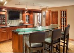This man cave includes a handsome bar area with built in wine cabinet and flat panel TV mounted in the wall for the ultimate party or sporting event. - CHC Creative Design & Remodeling