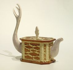 """Michael Massie (1962- ), Canadian / """"oc-tea-gon teapot"""" ... fish design on irregular octagon box shape body lashed together w/ sinew like a traditional grub box tied to a sled, bone shape handle and knob, c. 2010s, spanish cedar, brass, antler, bone, sinew ... Massie is a Newfoundland artist/silversmith of mixed Inuit, Métis and Scottish heritage"""