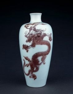 Porcelain vase of meiping form. Underglaze red and blue with two vertical five-clawed dragons painted red with dark blue eyes and tail details. Inscription on base.