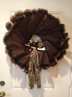 """Great wreath idea... made with turkey tail feathers, camo """"bow"""" from an old T-shirt, and a wing bone call."""