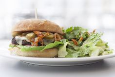 Vegetarian Black Bean Burger   pepper jack cheese, caramelized chipotle onion, tomato, lettuce, pickled jalapenos served with small chili lime Caesar salad, tortilla chips and salsa