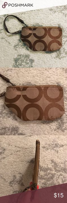Brown & beige Coach clutch wristlet purse Brown and beige/tan Coach C clutch wristlet purse. Top zip enclosure. The wristlet measures 4.25 inches tall and 7 inches wide. The pattern on the exterior of the purse is C's in big block letters with the word Coach stitched on in cursive font in random parts. The interior of the purse has beige fabric lining with the Signature Coach C print on it in brown. Some wear with use, but in good condition with a lot of life left in it! Coach Bags Clutches…