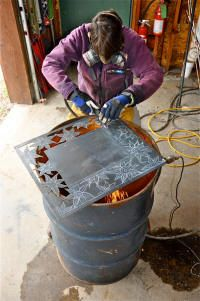 The artist creating fine metal art with a cutting torch