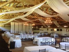 Cafe lights in straight lines Sunset Ranch Chandeliers and Draping in ceiling and back partition. (@sunsetranchHI Barn)