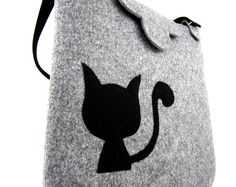 The bag was made from stabilized felt. Felts thickness is 0.16 / 4mm, so the bag keep its shape. To carry in hand and shoulder. There are two pockets, one for mobile phone. There are also places for pens. In front of bag there is one pocket and original two black cats, The bag doesnt have a lining. Its closed with zipper.  Dimensions: - width: 15,5 / 40 cm - height: 13 / 33 cm - length of holder: 21.5 / 55 cm - width of the base: 4 / 10 cm - length of belt: max 47 / 120 This item will be…